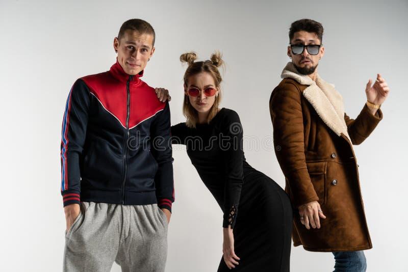 Unga vänner som har gyckel tillsammans, härlig kvinna som står mellan två stiliga män royaltyfri foto