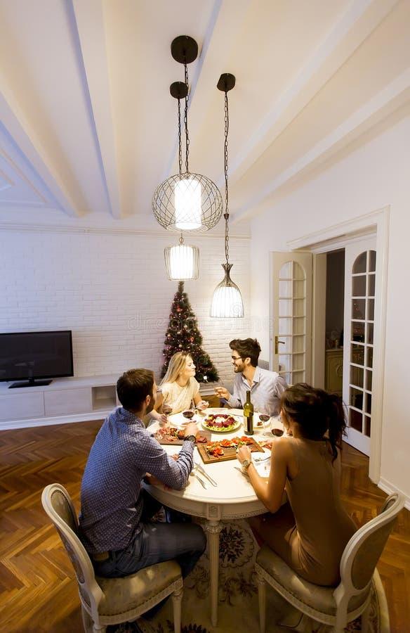 Unga vänner som hemma firar helgdagsafton för jul eller för nytt år royaltyfri foto