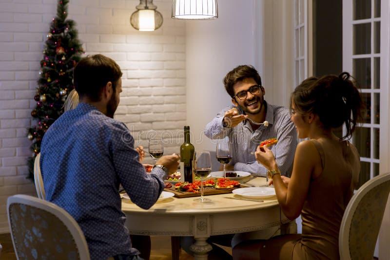 Unga vänner som hemma firar helgdagsafton för jul eller för nytt år arkivbild