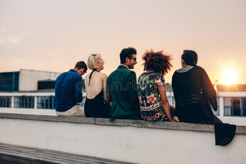 Unga vänner som kopplar av på terrass under solnedgång royaltyfri bild
