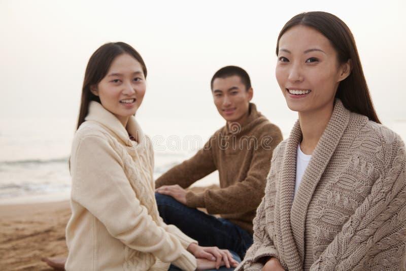 Unga vänner som sitter på stranden royaltyfria bilder
