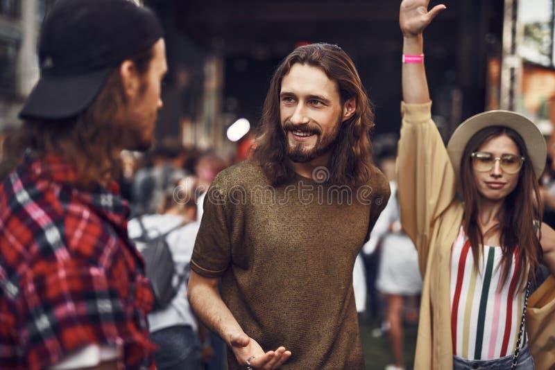 Unga vänner som spenderar tid på den utomhus- konserten arkivbild