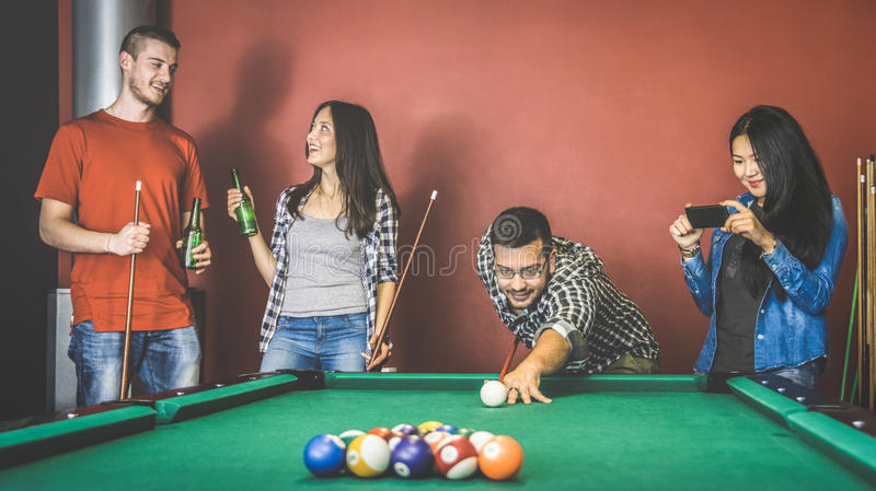 Unga vänner som talar och spelar pölen på salongen för billiardtabell arkivbilder