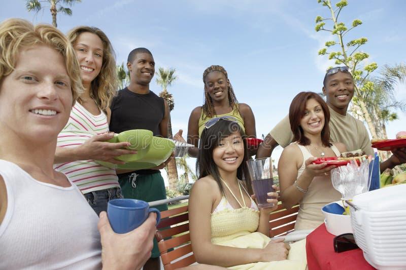 Unga vänner som tillsammans äter royaltyfri foto