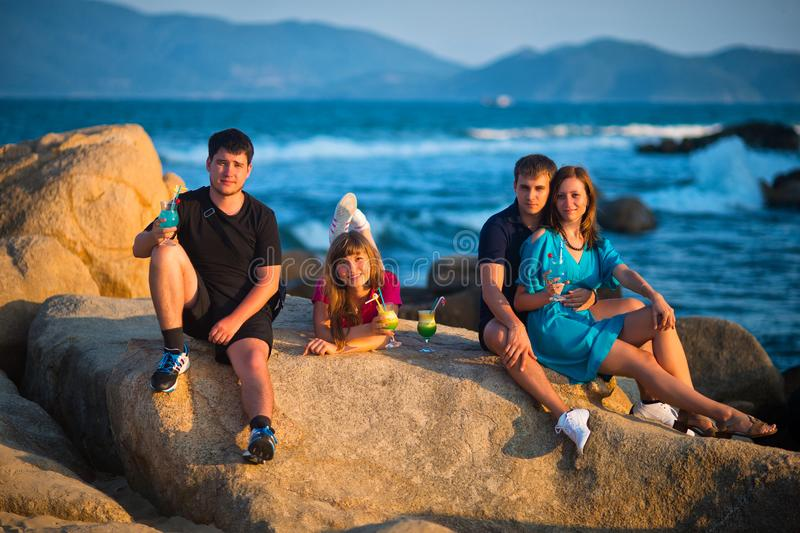 Unga vänner som vilar på stora stenblock mot havet royaltyfria bilder
