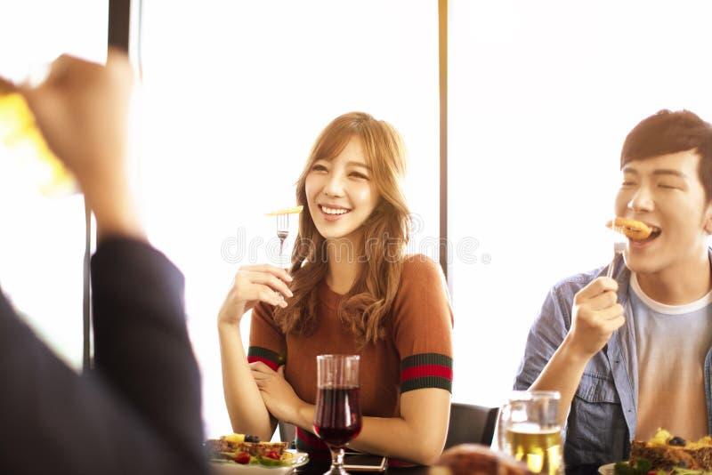 unga vänner tycker om matställen i restaurang royaltyfria bilder