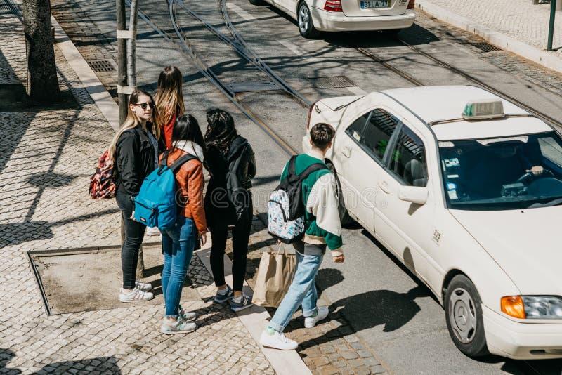 Unga vänturister med ryggsäckar ska stiga ombord en stadstaxi arkivfoto