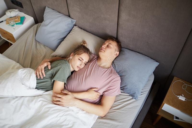 Unga vilsamma romantiska par som tillsammans sover i säng arkivfoton