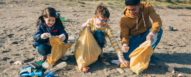 Unga volont?rer som g?r ren stranden royaltyfri foto