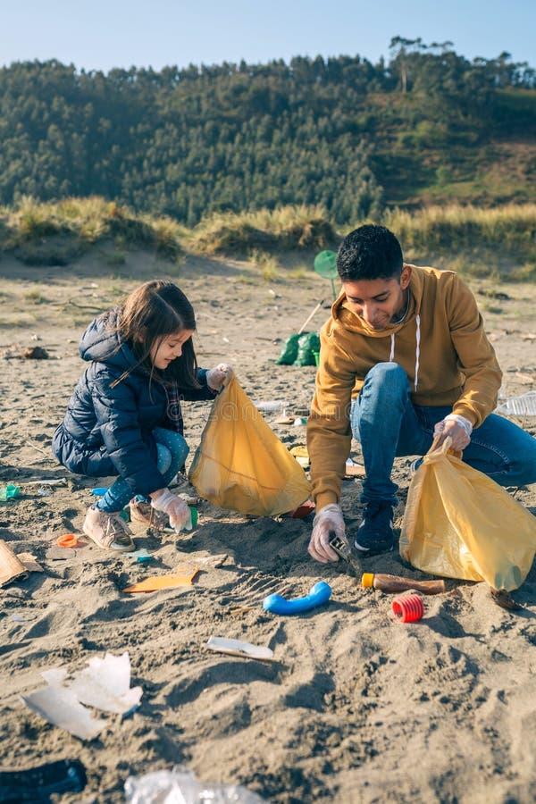 Unga volont?rer som g?r ren stranden royaltyfria bilder