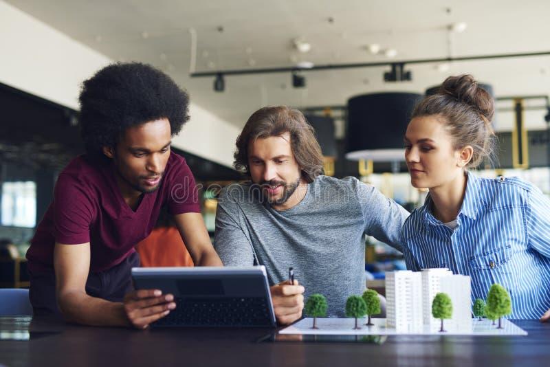 Unga vuxna kollegor som arbetar på kontorsskrivbordet royaltyfria bilder