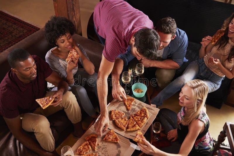 Unga vuxna människor som äter pizza på ett hemmastatt parti, högstämd sikt fotografering för bildbyråer