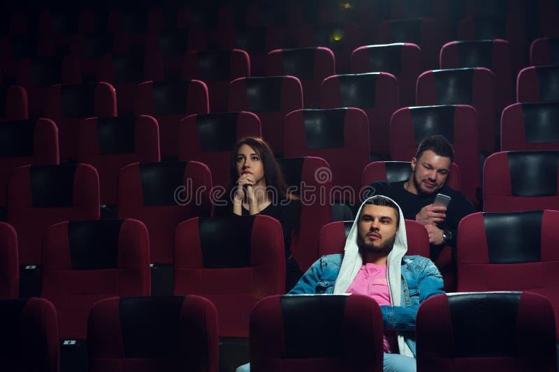 Unga vuxna människor som håller ögonen på den tråkiga filmen i filmbiograf fotografering för bildbyråer