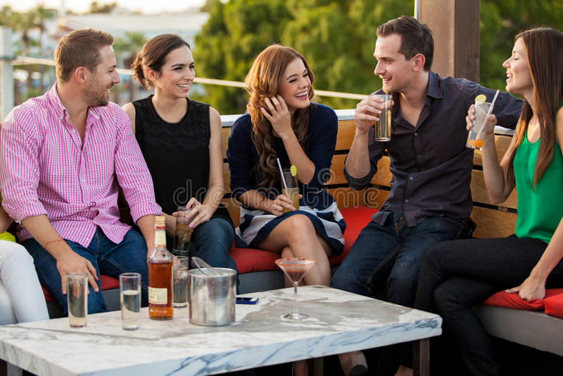 Unga vuxna människor som har drinkar på en stång royaltyfri bild