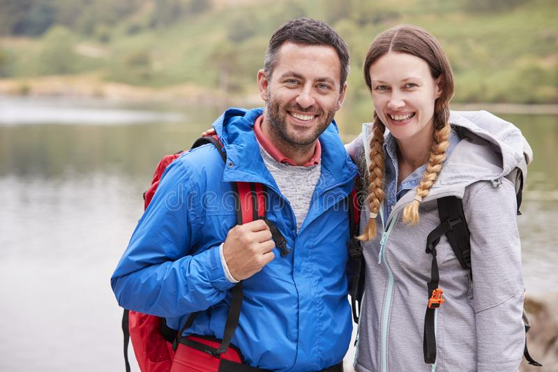 Unga vuxna par på en campa tur som står nära en sjö som ser till kameran, slut upp, sjöområde, UK royaltyfria bilder