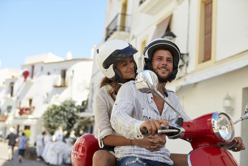 Unga vuxna par på en motorisk sparkcykel i en gata, Ibiza arkivfoto