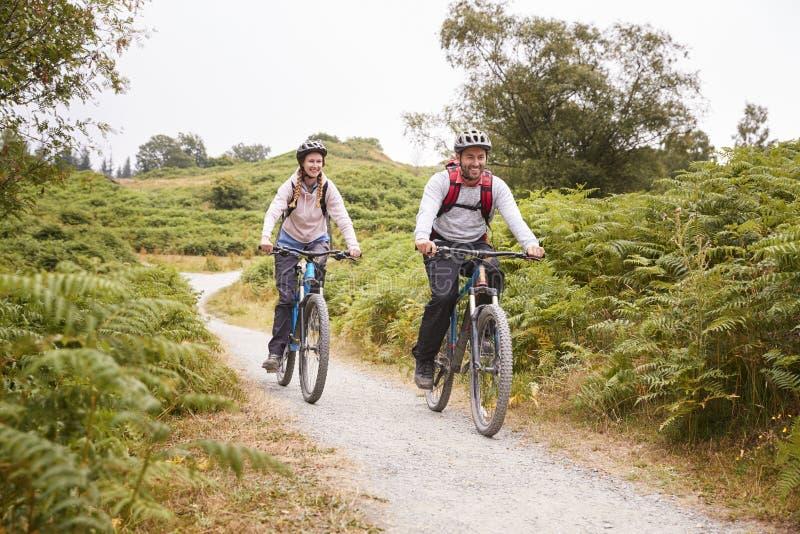 Unga vuxna par som rider mountainbiken i bygden, full längd royaltyfri fotografi