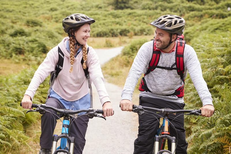 Unga vuxna par som rider mountainbiken i en landsgränd som ser sig, tätt upp royaltyfria bilder