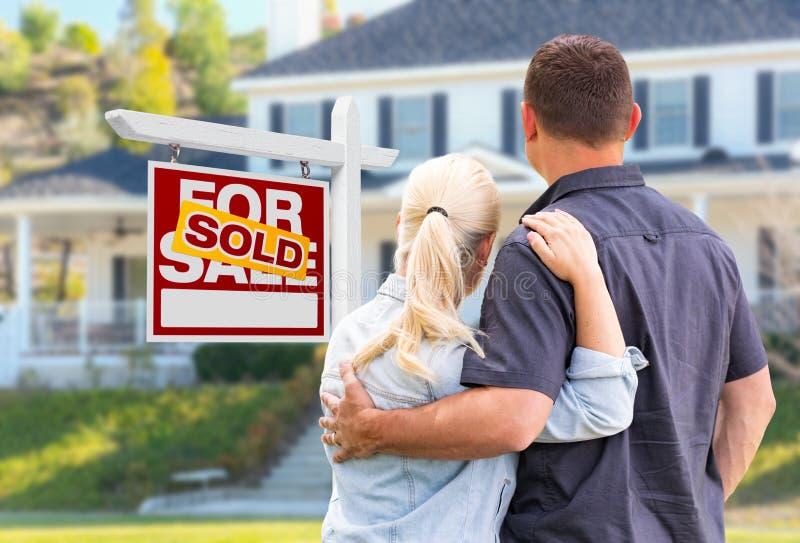 Unga vuxna par som vänder mot framdelen av det sålda Real Estate tecknet royaltyfri foto
