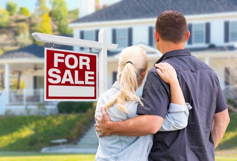 Unga vuxna par som vänder mot framdelen av det till salu Real Estate tecknet royaltyfria foton