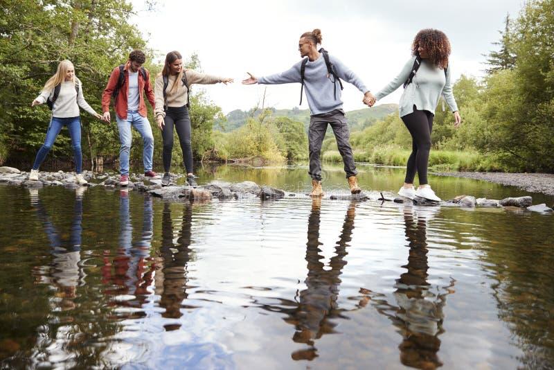 Unga vuxna vänner som når för att hjälpa sig att korsa en ström som balanserar på stenar under en vandring royaltyfri bild