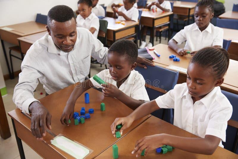 Ungar för lärareportiongrundskola som räknar med kvarter royaltyfri bild