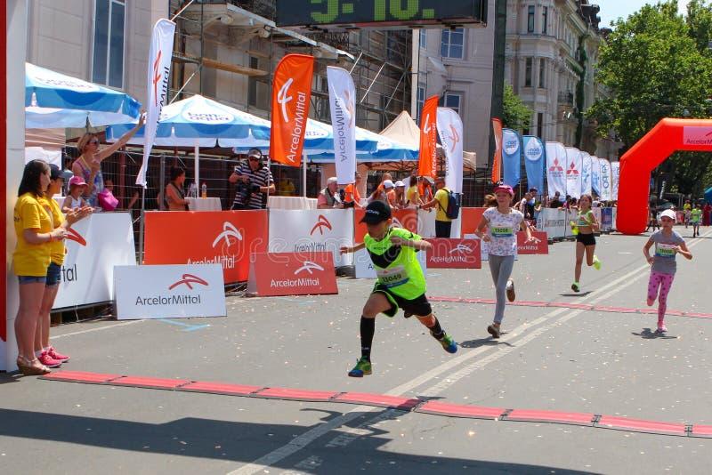 Ungar för maratonlöpare korsar mållinjen på den soliga sommardagen arkivfoton