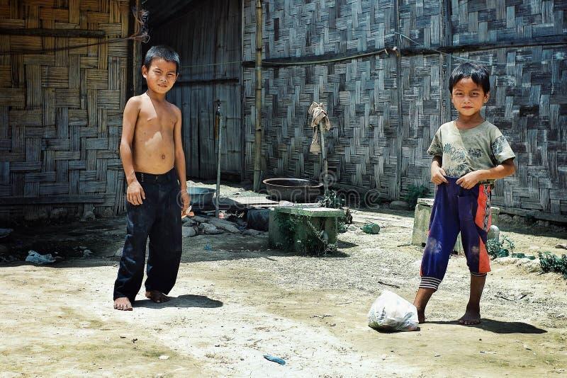 ungar från lolostammen som spelar fotboll med en plastpåse, fyllde med avfall royaltyfri foto