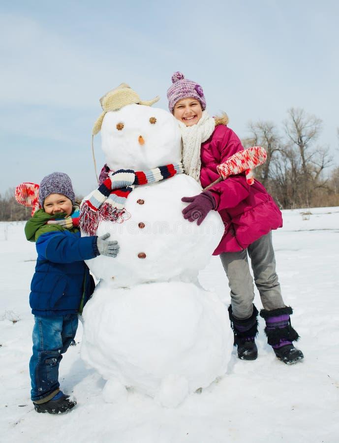 Ungar gör en snögubbe arkivbilder