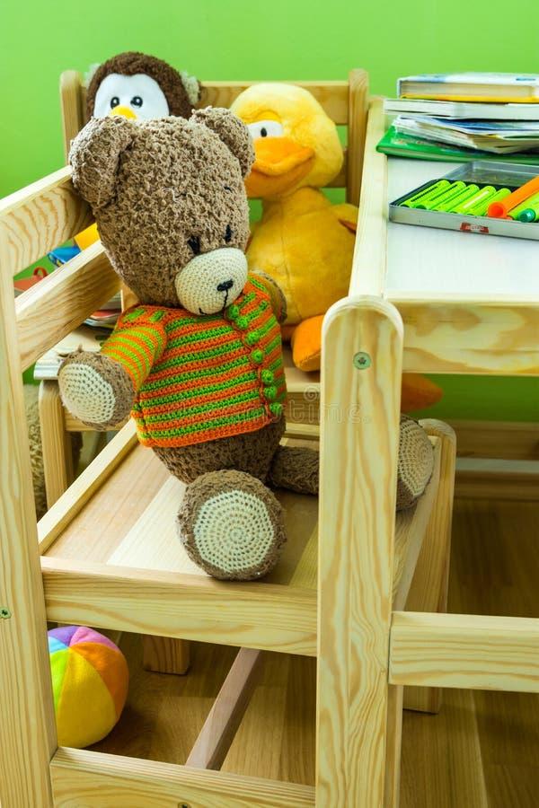 Ungar hyr rum inre, trämöblemanguppsättningen, nallebjörn på stol, flotta leksaker, böcker, färgpennor på tabellen royaltyfri foto