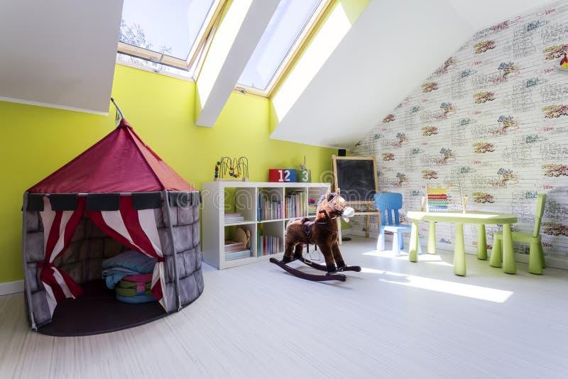 Ungar hyr rum med lektältet och en vagga häst fotografering för bildbyråer