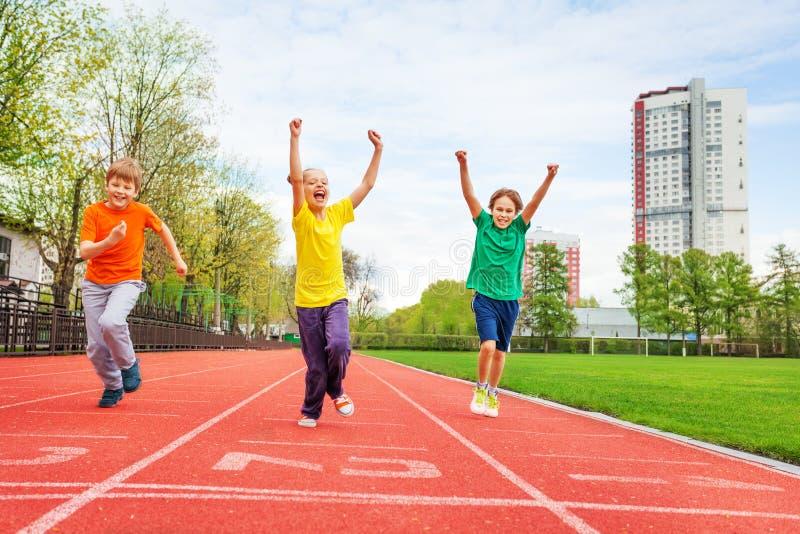 Ungar i färgrika likformig med armar up spring royaltyfria bilder