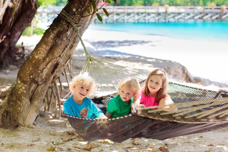 Ungar i h?ngmatta Barn p? den tropiska stranden arkivfoto