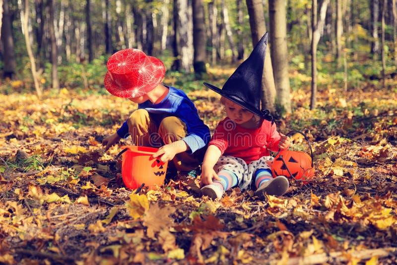 Ungar i halloween dräktlek på hösten parkerar, tricket eller behandling arkivbild