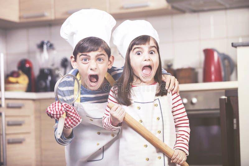 Ungar i kockhattar i köket royaltyfria bilder