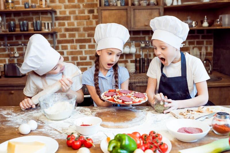 Ungar i kockhattar som gör pizza fotografering för bildbyråer