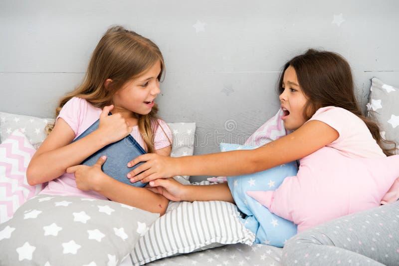 Ungar lägger i sängkampen för bok Vänner har några problem Moment för att handla med siblingrivalitet Det finns inte någon skada  royaltyfri bild