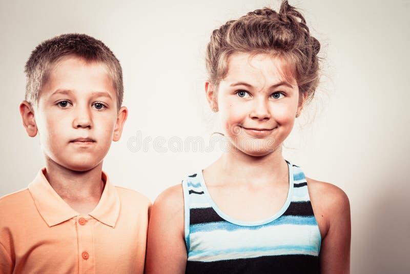Ungar liten flicka och uttryck för framsida för pojkedanande enfaldigt royaltyfria foton