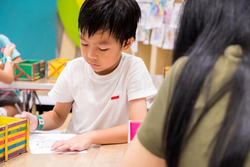 Ungar målar bilden med färgblyertspennan med deras lärare i klassrumet för att lära målarfärgexpertis de är övning royaltyfria foton