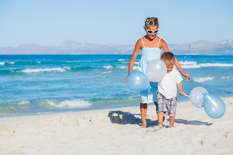Ungar med ballons på stranden fotografering för bildbyråer