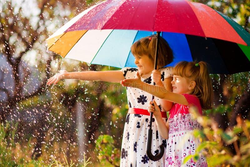 Ungar med det färgrika paraplyet som spelar i höstduschregn Små flickor spelar parkerar in vid regnigt väder arkivbild