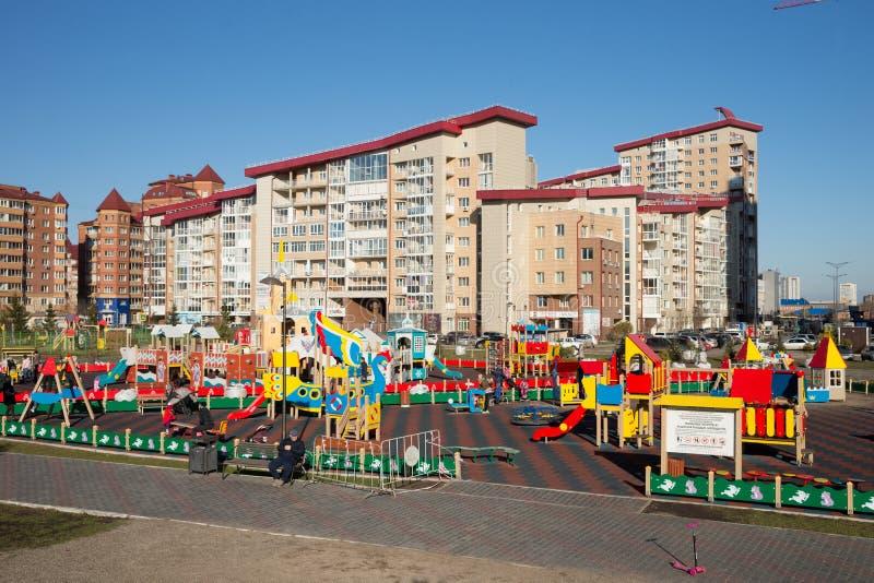 Ungar med föräldrar spelar på en offentlig lekplats i ett bostadsområde av ‹Krasnoyarsk för †på en solig höstdag arkivfoton