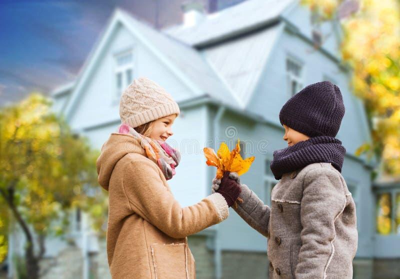 Ungar med höstlönnlöv över hus utomhus arkivbilder