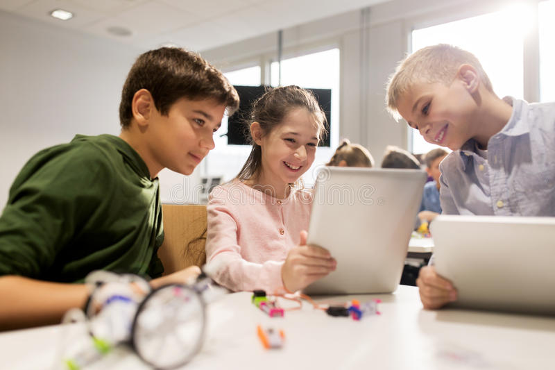 Ungar med minnestavlaPC:n som programmerar på robotteknikskolan royaltyfri bild
