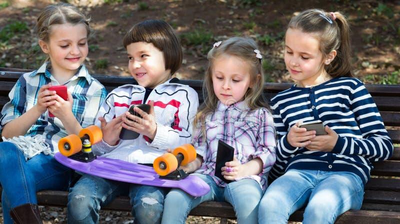 Ungar med utomhus- mobila enheter royaltyfria bilder