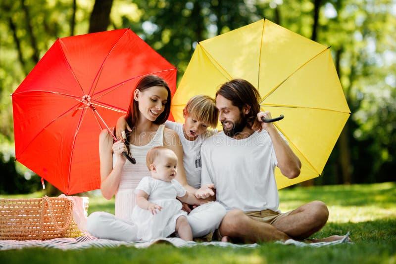 Ungar och deras föräldrar som sitter på filten under de stora röda och gula paraplyerna som täcker dem från solen royaltyfri fotografi