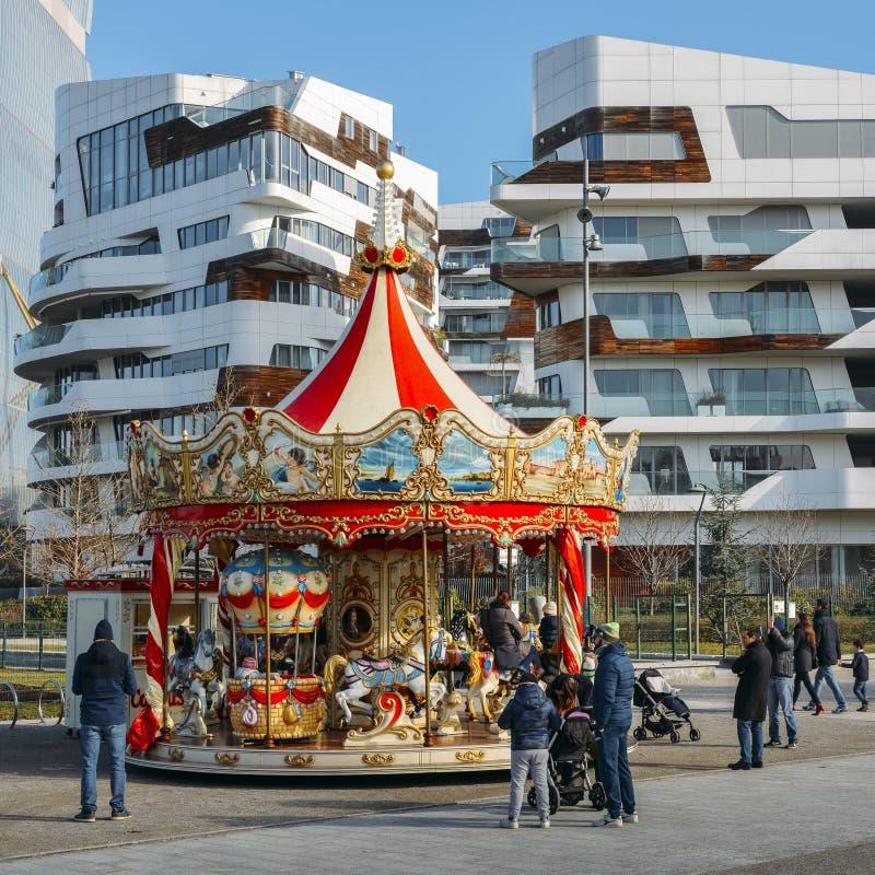 Ungar och familjlek i en karusell ställde in i det Tre Torri Citylife området av Milan, Italien under en solig vinterdag royaltyfria foton