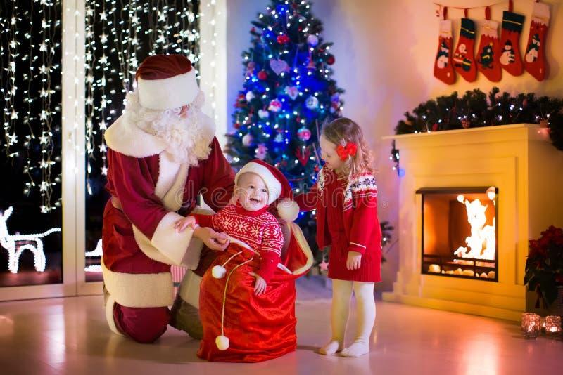 Ungar och jultomten som öppnar julklappar royaltyfri foto