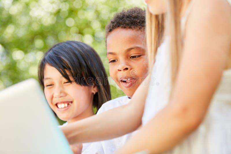 Ungar på bärbara datorn har roligt prata royaltyfri bild