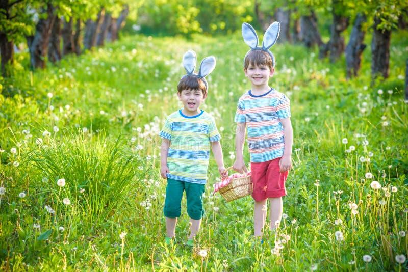 Ungar på jakt för påskägg i blommande vår arbeta i trädgården Barn bryner arkivbild